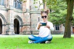 拍照片的年轻十几岁的女孩在格拉斯哥大学庭院里 库存照片