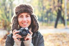 拍照片的年轻女人在秋天公园 免版税图库摄影