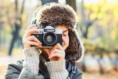 拍照片的年轻女人在秋天公园 免版税库存照片