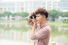 拍照片的年轻微笑的人,当走由城市时 库存图片