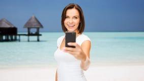 拍照片的愉快的妇女由在海滩的智能手机 免版税库存照片