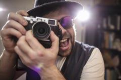 拍照片的愉快的微笑的摄影师行家使用老猪圈 库存照片