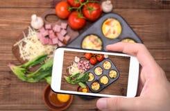 拍照片的手怂恿松饼用火腿、乳酪和菜与智能手机 库存图片