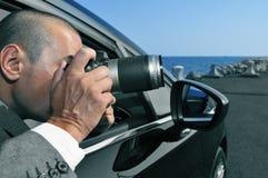 拍照片的探员或无固定职业的摄影师从汽车里边 免版税库存照片