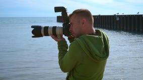 拍照片的摄影师在海海滩 关闭有照相机的摄影师 股票视频