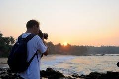拍照片的摄影师在海滩 库存图片