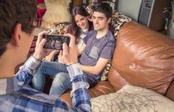 拍照片的朋友对在沙发的少年夫妇 库存照片