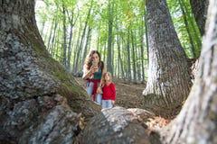拍照片的母亲和孩子在森林里 免版税库存图片