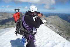 拍照片的登山人在到达山顶以后 免版税库存图片