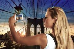 拍照片的白肤金发的旅游女孩在布鲁克林大桥 库存照片