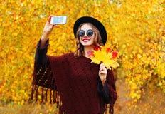 拍照片的秋天时尚微笑的少妇在晴朗的黄色叶子的智能手机做自画象 图库摄影