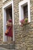 拍照片的红色礼服的女孩在Ainsa,西班牙村庄  库存照片