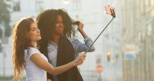 拍照片的美丽的微笑的不同种族的女朋友的水平的侧视图使用在街道的selfie棍子 股票录像