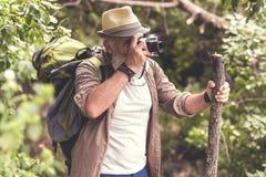 拍照片的老人由照相机在森林里 免版税库存图片