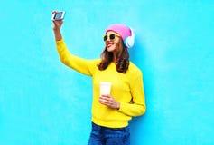 拍照片的耳机听的音乐的时尚凉快的微笑的女孩在穿五颜六色的衣裳的智能手机做自画象 库存图片