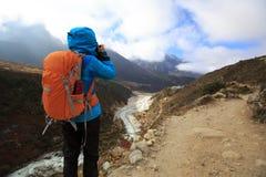 拍照片的背包徒步旅行者,当迁徙在喜马拉雅山山时 免版税库存图片