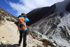 拍照片的背包徒步旅行者,当迁徙在喜马拉雅山山时 免版税库存照片