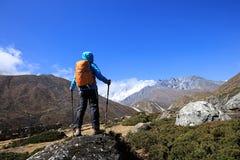 拍照片的背包徒步旅行者,当迁徙在喜马拉雅山山时 库存照片