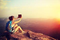拍照片的远足者用途数字式片剂在山峰峭壁 免版税库存照片