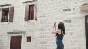 拍照片的雍妇女由智能手机 有户外电话的时髦的夏天旅客妇女在欧洲城市,老镇 库存图片