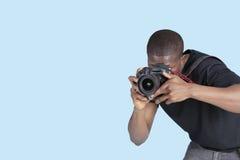 拍照片的年轻人通过在蓝色背景的数字照相机 免版税图库摄影
