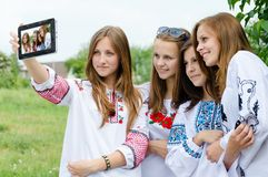 拍照片的他们自己的四个相当青少年的女孩 免版税库存照片