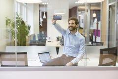 拍照片的Selfie偶然商人在露天场所办公室 库存照片