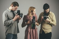 拍照片,夺取魔术 减速火箭的样式妇女和人拿着模式照相机 无固定职业的摄影师或摄影记者与 库存图片