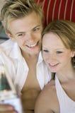 拍照相机自已的电话照片在沙发大角度视图的年轻夫妇 免版税库存图片