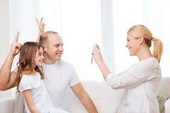 拍父亲和女儿的照片愉快的母亲 免版税库存照片