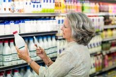 拍牛奶瓶的照片资深妇女 免版税库存图片