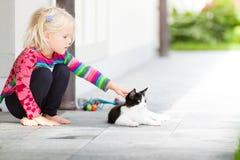 轻拍猫的俏丽的女孩外面 免版税图库摄影
