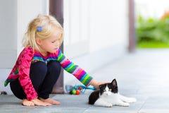 轻拍猫的俏丽的女孩外面 免版税库存照片