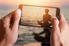 拍瑜伽妇女的照片男性手meditatiing在海滩的莲花姿势在与细胞,手机的日落期间 库存图片