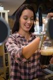 从轻拍的微笑的年轻女服务员倾吐的饮料在玻璃 库存图片