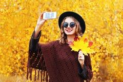 拍秋天照片的画象时尚微笑的少妇在晴朗的黄色叶子的智能手机做自画象 免版税库存照片