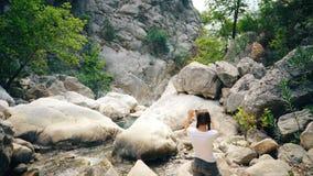拍美丽的峡谷的照片在她的智能手机照相机的年轻旅游妇女在旅行期间 影视素材