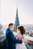 轻拍美丽的握有花束的新娘和新郎手看彼此在古老阳台 免版税库存图片
