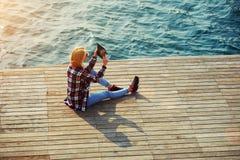 拍美丽的景色的照片的与她的照相机片剂的年轻旅游妇女 库存图片