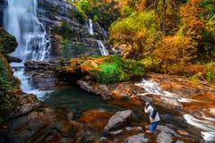 拍美丽的瀑布的照片摄影师在秋天 免版税库存照片