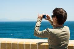 拍蓝色海的照片妇女 免版税库存图片