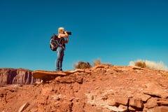 拍风景照片的妇女在站立在岩石的亚利桑那 图库摄影