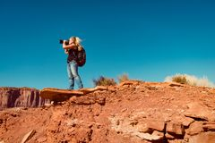 拍风景照片的妇女在站立在岩石的亚利桑那 免版税库存图片