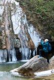 拍冻冬天瀑布的照片女性远足者,站立在岩石 免版税库存照片
