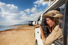 拍从徒步旅行队吉普窗口的女孩照片  图库摄影