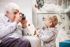 拍他的小孩孙子的照片老人 免版税库存照片