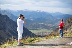 拍他的山的儿子的照片年轻父亲 免版税库存照片