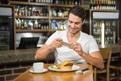 拍他的食物的照片英俊的人 免版税库存照片