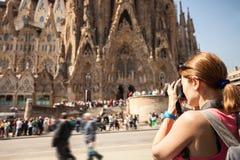 拍Sagrada Familia,巴塞罗那,西班牙的照片少妇 免版税库存图片