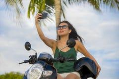 拍selfie与手机照相机骑马滑行车摩托车的年轻愉快和相当亚裔中国妇女画象照片 库存图片